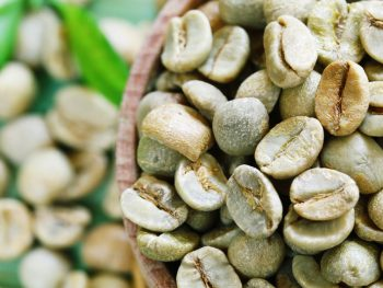 green coffee beans on a wooden background