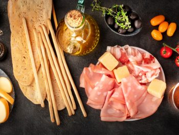 food flatlay with charcuterie boards, pasta, bread, tomatoes and more food items on a black background