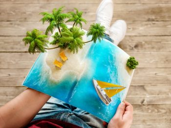 Tropical island with palms and deck chairs on a page of opened magazine in hands. Unusual travel 3d illustration. Summer travel and vacation concept