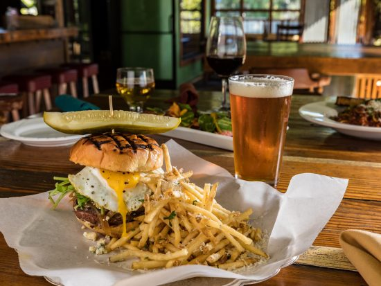 huge burger with fries and a pint of amber beer on a table at flying pig in oceanside